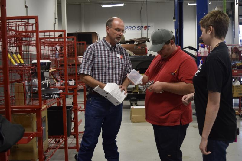 (Left to right) Kevon Kleibrink, an instructor in the Auto Collision and Management Technology program at Texas State Technical College in Waco, talks to Auto Collision Management and Technology majors (center) Justin Hathcock of Hico and (right) Victoria Betts of Whitehouse about new equipment.
