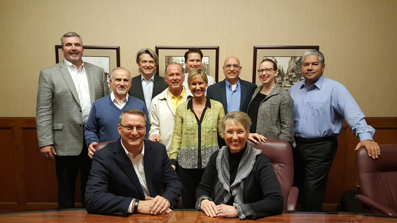 Michael Cash (seated left), Senior Vice President and President, Industrial Coatings of Axalta Coating Systems and Sandy Berg, President and CEO of Ellis Paint Company, joined by members of Axalta and Ellis management.